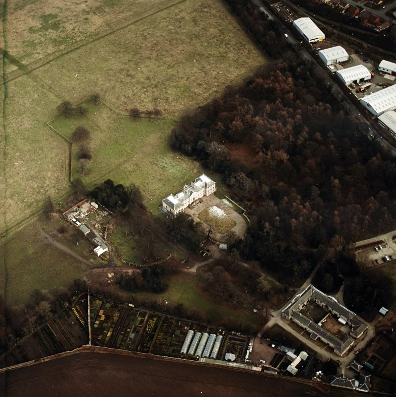 Oblique aerial view centred on the country house with walled garden, stables, cottage, formal garden and dovecot adjacent, taken from the W.