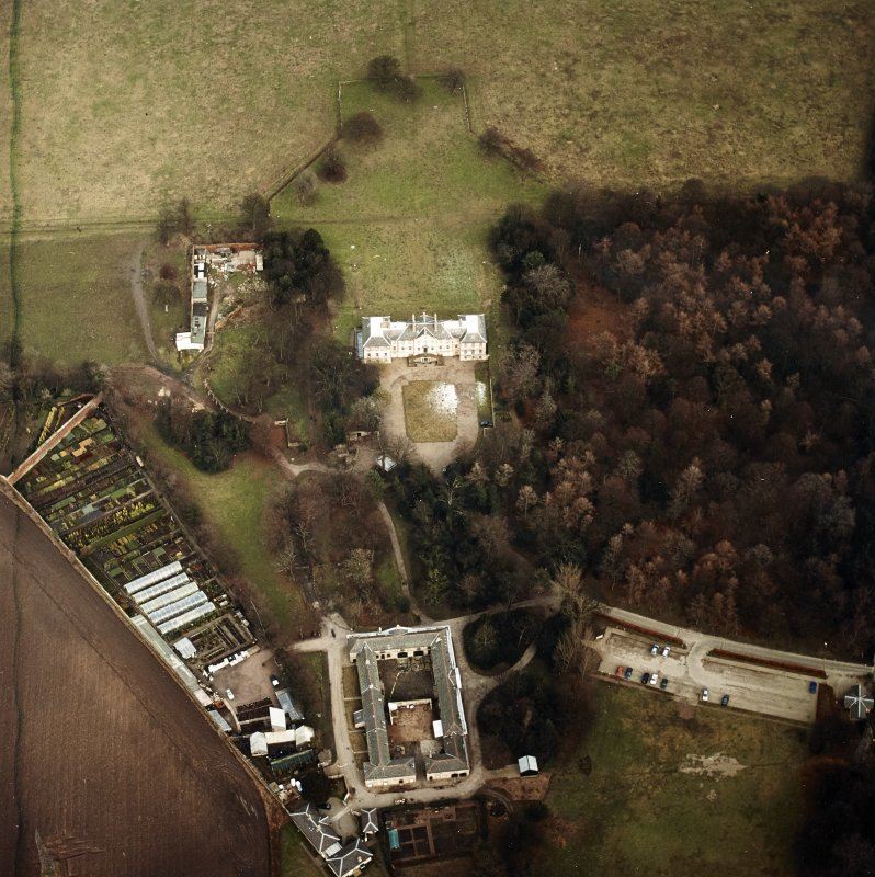 Oblique aerial view centred on the country house with walled garden, stables, cottage, formal garden, gate lodge and dovecot adjacent, taken from the SW.