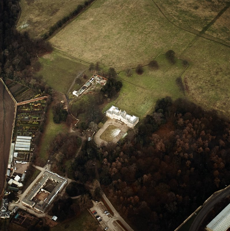 Oblique aerial view centred on the country house with walled garden, stables, cottage, formal garden and dovecot adjacent, taken from the SW.