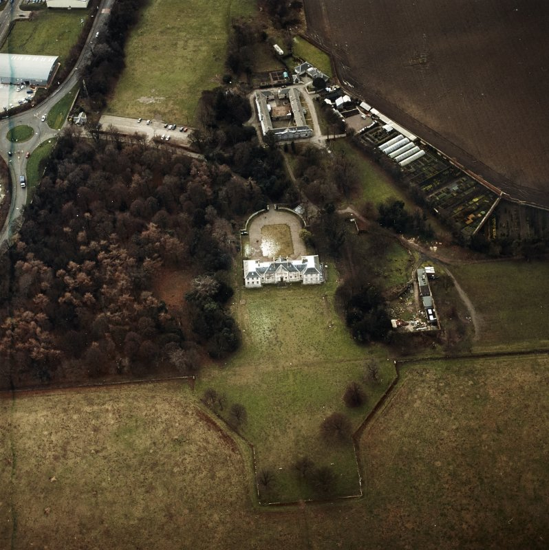 Oblique aerial view centred on the country house with walled garden, stables, cottage, formal garden, gate lodge and dovecot adjacent, taken from the NE.