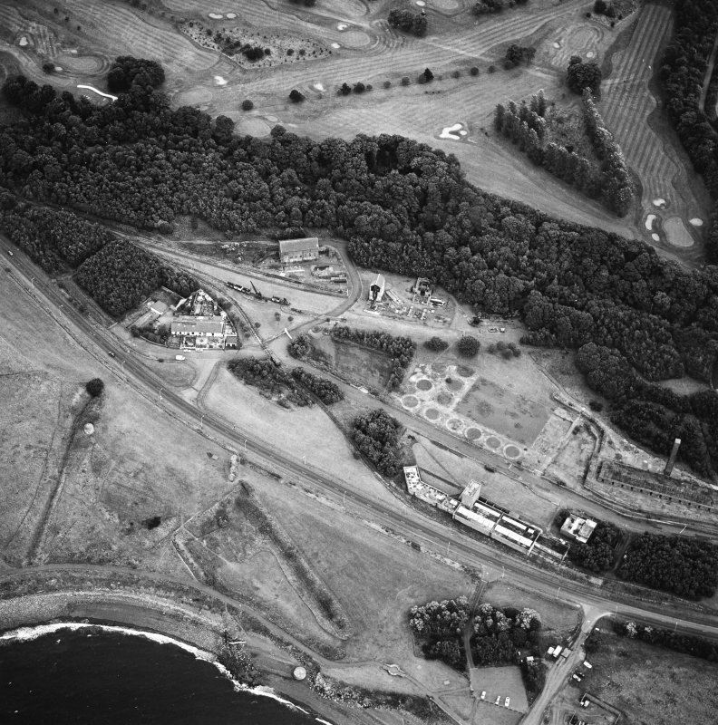 Oblique aerial view centred on the museum and remains of the coal mine, brick-works, tile-works and harbour, taken from the NW.