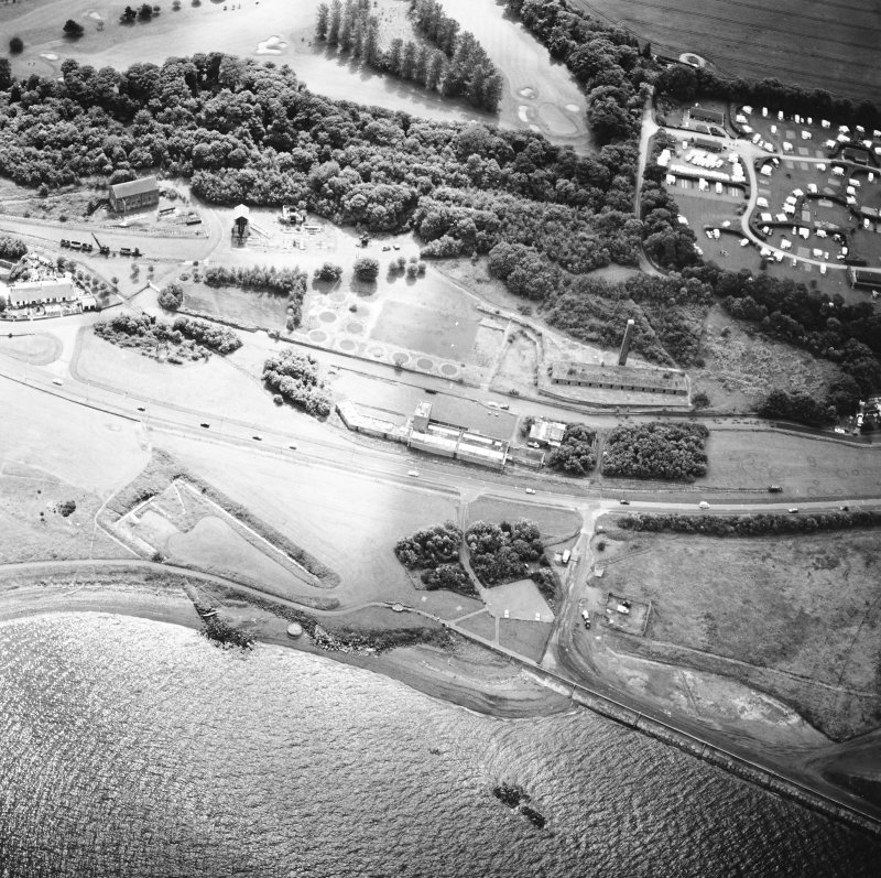 Oblique aerial view centred on the museum and the remains of the coal mine, brick and tileworks and harbour, taken from the NW.