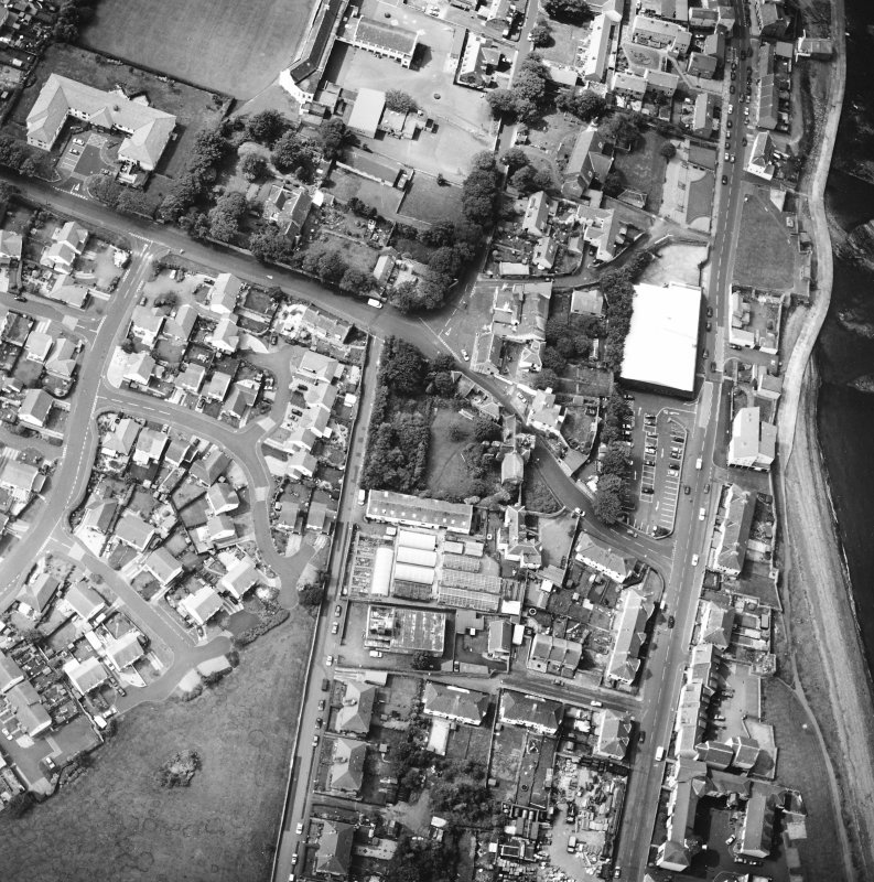 Oblique aerial view centred on the house and stables with the church adjacent, taken from the NE.