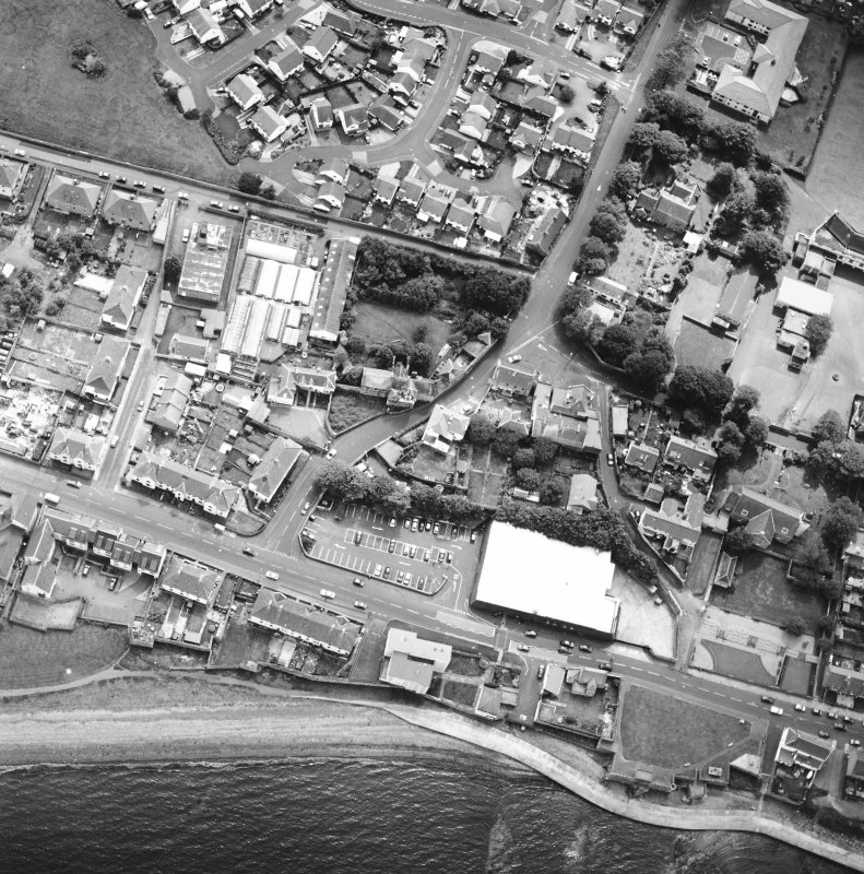 Oblique aerial view centred on the house and stables with the church adjacent, taken from the NW.