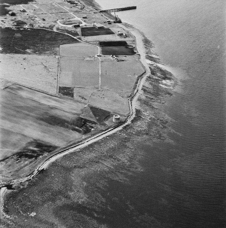 Hoy, Crockness, oblique aerial view, taken from the ESE, centred on the Martello Tower and a curving linear soilmark, and showing Rinnigill Military Camp and a crane in the background.