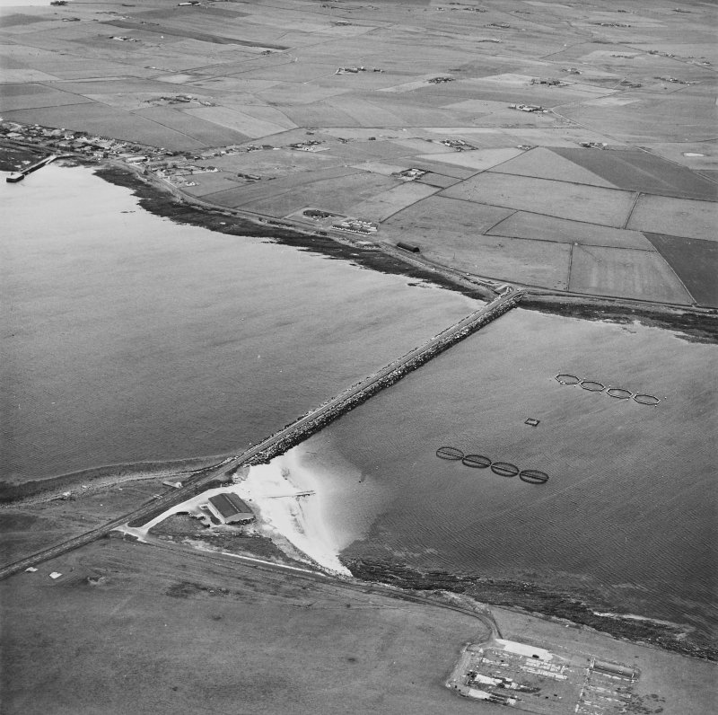 Oblique aerial view from ESE, centred on the Barrier, and showing The Italian Chapel, and the remains of Lamb Holm Military Camp, in the bottom right-hand corner of the photograph.