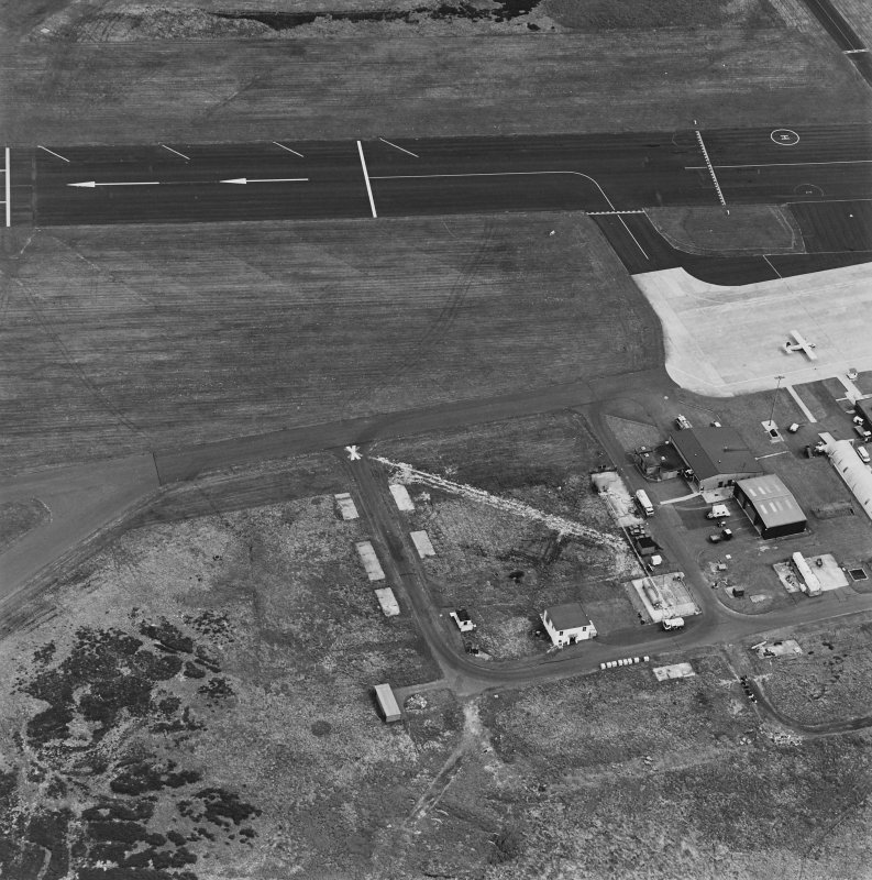 Oblique aerial view from SW.  Visible are several concrete hut bases, Nissen hut and modern additions.