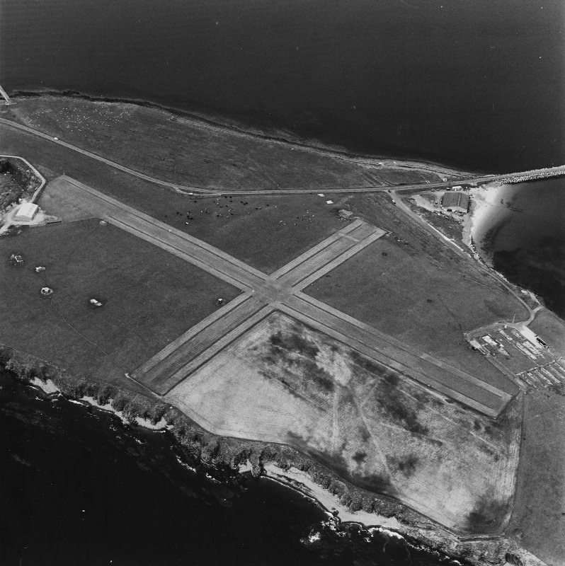 Oblique aerial view, Orkney, Lamb Holm taken from the SE.  Visible is the modern grass landing strip, Lamb Holm World War II coast battery, the concrete hut bases of the former prisoner-of-war camp, the Italian Chapel and part of Churchill Barrier No.1.