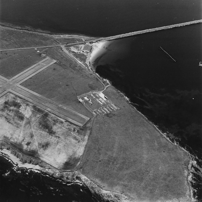 Oblique aerial view, Orkney, Lamb Holm taken from the SE.  Visible is the modern grass landing strip, the concrete hut bases of the former prisoner-of-war camp, the Italian Chapel and part of Churchill Barrier No.1.