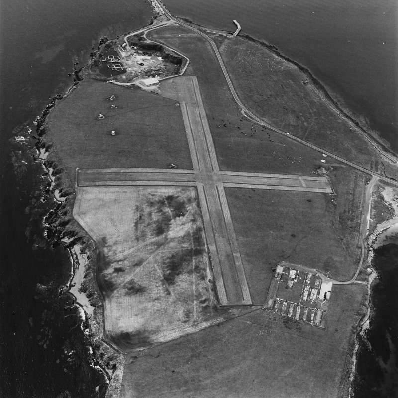 Oblique aerial view, Orkney, Lamb Holm taken from the NE.  Visible is the modern grass landing strip, Lamb Holm World War II coast battery, the concrete hut bases of the former prisoner-of-war camp, the Italian Chapel and part of Churchill Barrier No.2.