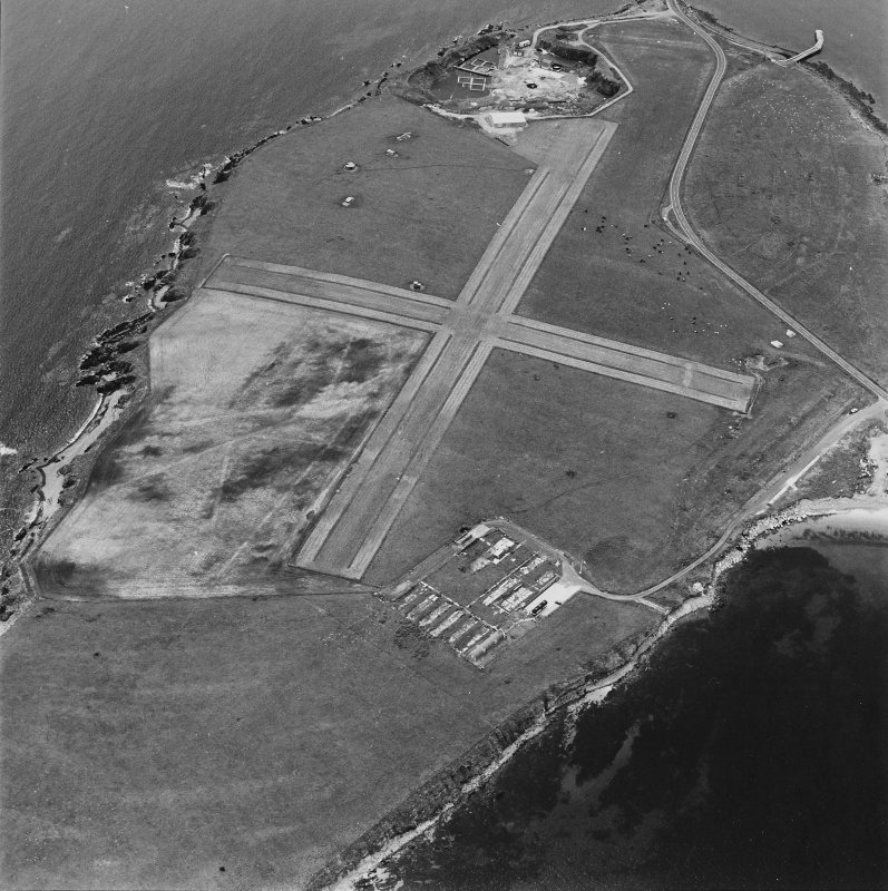 Oblique aerial view, Orkney, Lamb Holm taken from the NNE.  Visible is the modern grass landing strip, Lamb Holm World War II coast battery, the concrete hut bases of the former prisoner-of-war camp, the Italian Chapel.