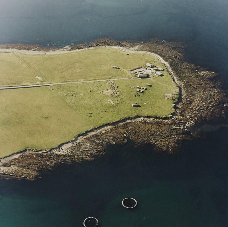 Oblique aerial view of Orkney, Car Ness, Car Ness and Wellington Batteries, from SE.  Visible are the gun-emplacements, battery observation towers, searchlight platforms and Nissen huts for both batteries. The site of a heavy anti-aircraft battery is just discernable to the S.