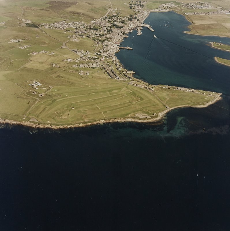 Oblique aerial view of the Second World War Ness and Links Batteries with the First World War Ness Battery situated on the golf course,  taken from the SW.  Also visible in the background is Stromness town and harbour.