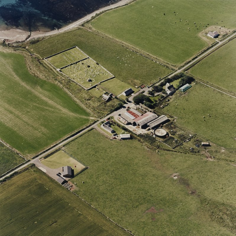 Oblique aerial view of Orphir, St Nicholas's Church, burial-ground and the Earl's Bu with mill, taken from the NE. Also visible is the Bu of Orphir farmhouse and farmsteading.