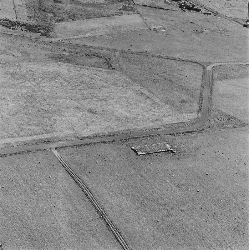 Oblique aerial photograph of part of Lyness Naval Oil Terminal taken from N showing footings of a large building.