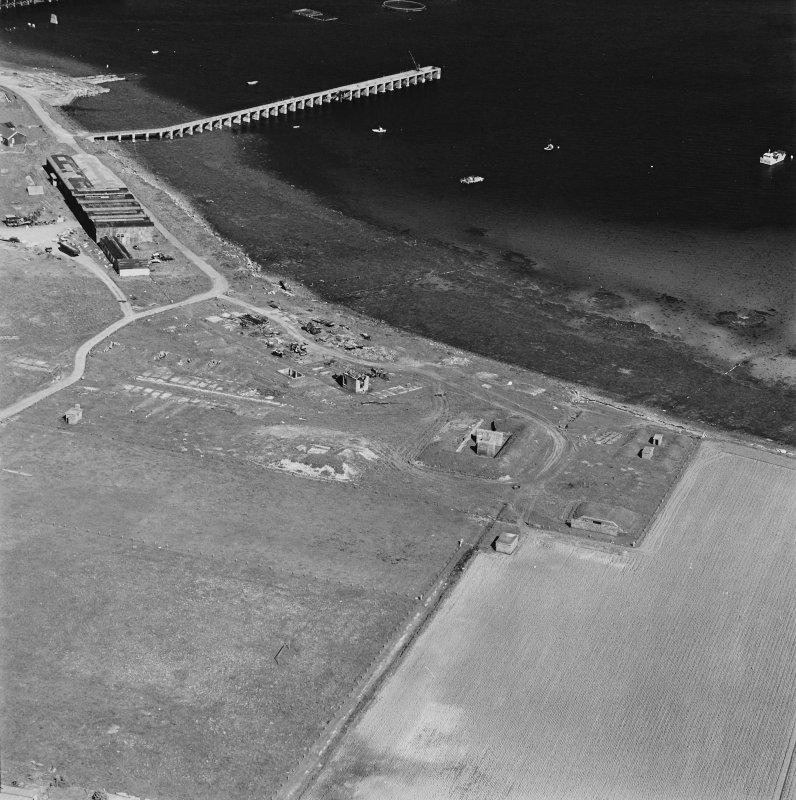 Aerial view of Orkney, Hoy, Lyness, Royal Naval Oil terminal, view from SW, of the site of the torpedo depot with a group of air raid shelters, generator house and several ancillery buildings. The former recreation centre, NAAFI and pier are in the background.