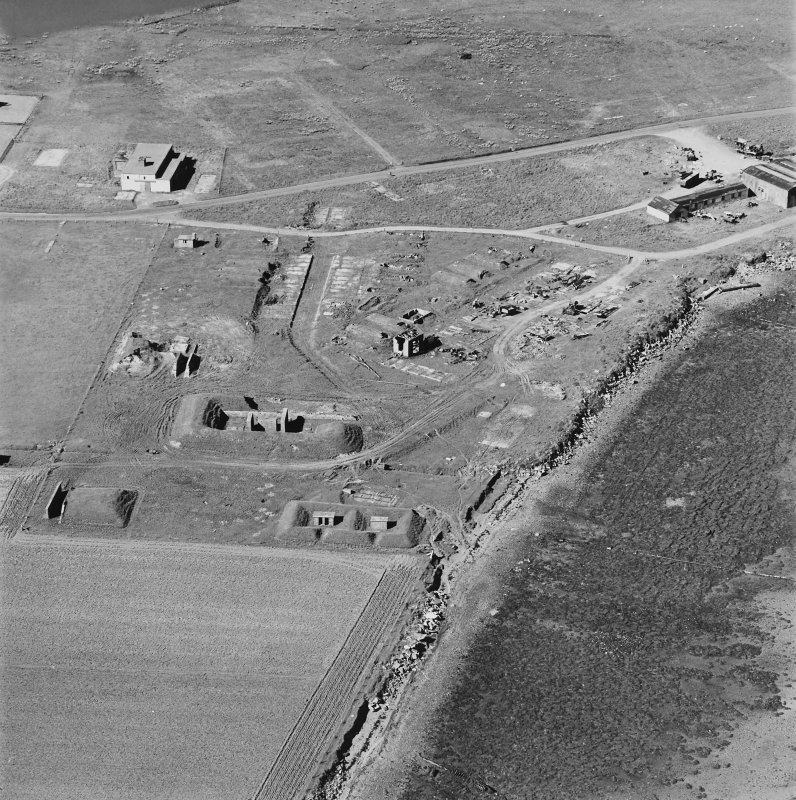 Oblique aerial view of Orkney, Hoy, Lyness, Royal Naval Oil Terminal, view from S, of the site of the torpedo depot with a group of air raid shelters, generator house and several ancillery buildings. Part of the former recreation centre, NAAFI are in the background.