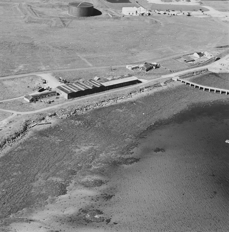 Oblique aerial view of Orkney, Hoy, Lyness, Royal Naval Oil Terminal, view from S, of the former recreation centre and NAAFI.  Part of the former boiler house, now the museum with the remaining oil tank is visible in the background.