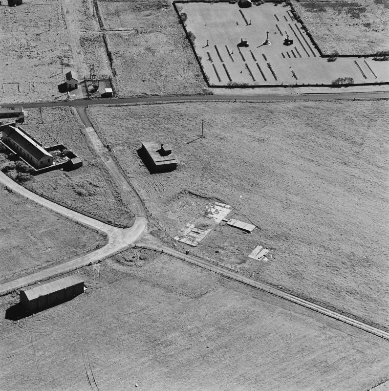 Oblique aerial view of Orkney, Hoy, Lyness, Royal Naval Oil Terminal, view from N, of buildings and a large concrete hut base with part of the Naval Cemetery.