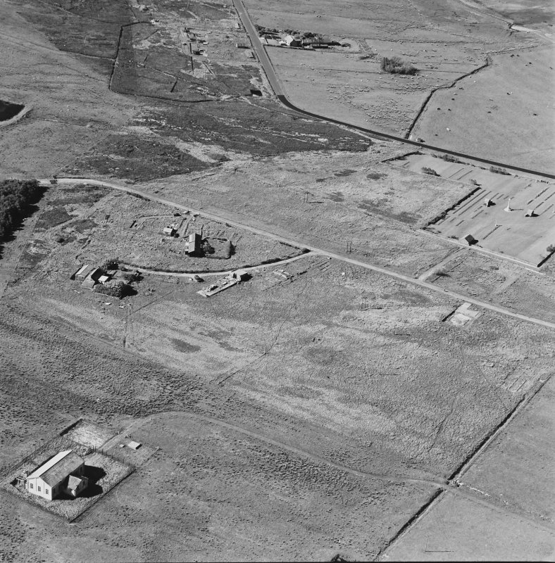 Oblique aerial view of Orkney, Hoy, Lyness, Royal Naval Oil terminal, view from S, of the Pumphouse for the underground oil tanks.  Part of the Naval Cemetery is visible in the background.