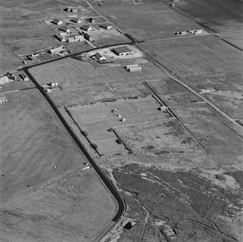 Oblique aerial view of Orkney, Hoy, Lyness, Royal Naval Oil terminal, view from NW, centred on Naval Cemetery and pillbox.