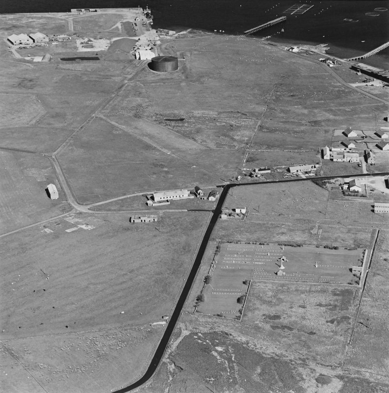 Oblique aerial view of Orkney, Hoy, Lyness, Royal Naval Oil Terminal, view of the Naval Cemetery and a pillbox.  Also visible are are some of the ancillary buildings and the remaining oil tank, museum complex in the N part of the Naval Base.