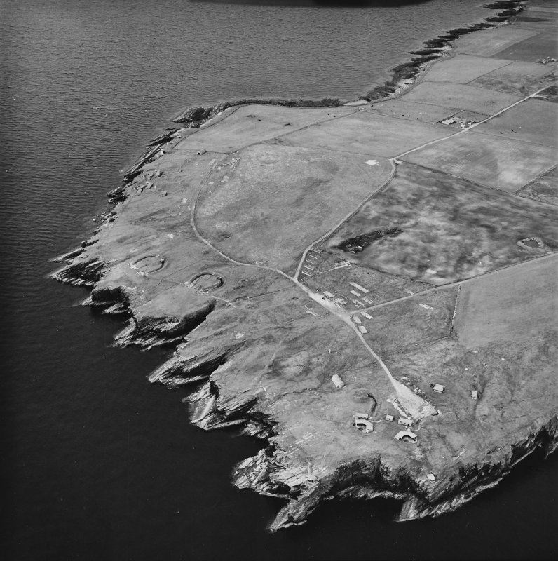 Oblique aerial view, taken from the SSW, centred on Hoxa Batteries and Camp Site, and showing Balfour Battery in the top left-hand corner area of the photograph.