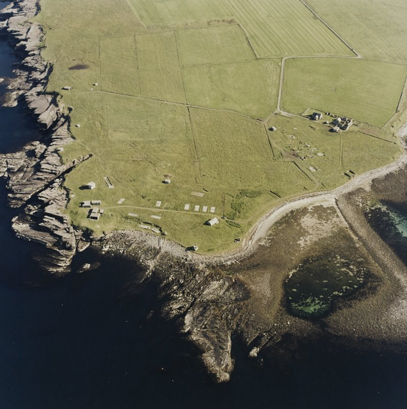 Oblique aerial view of Orkney, Rerwick Head, Rerwick Battery, taken from the N.  Visible are the gun-emplacements, battery observation tower, searchlight platforms, concrete hut bases for the accommodation camp and two air-raid shelters cut into the shore..