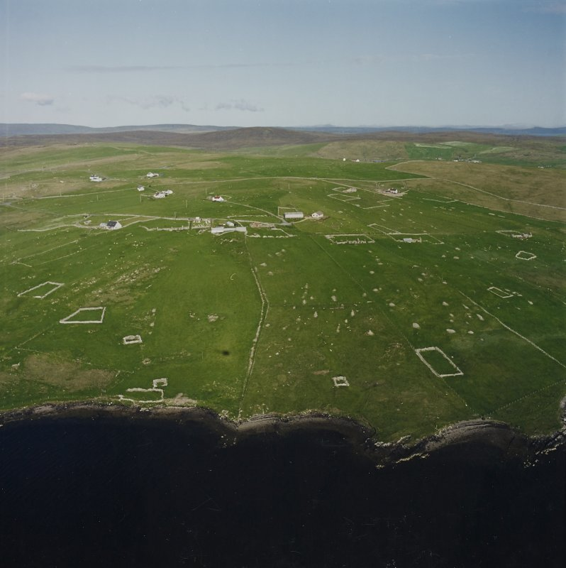Oblique aerial view centred on the remains of the township, chapel,  burial ground and head-dyke, taken from the WNW.