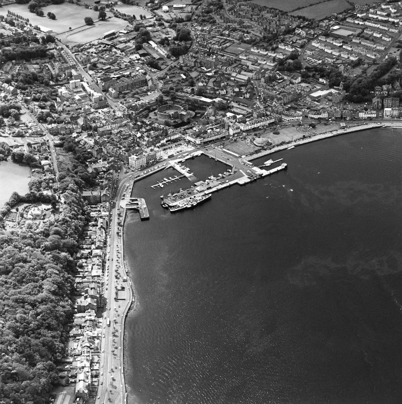 Oblique aerial view of Rothesay, taken from the NE, centred on a harbour.  A castle and the Winter Gardens are visible, in the top centre and centre of the photograph, respectively.