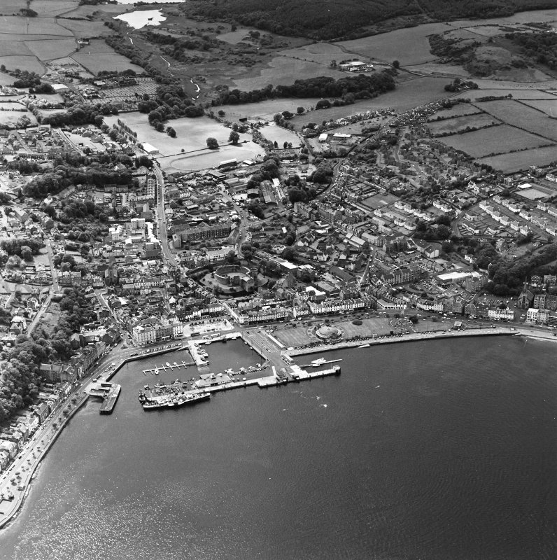 Oblique aerial view of Rothesay, taken from the N, centred on the town.  A harbour is visible in the bottom half of the photograph. A caslte and Winter Gardens are visible in the centre of the photograph.