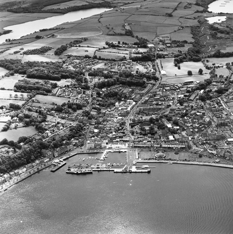 Oblique aerial view of Rothesay, taken from the N, centred on the town.  A harbour is visible in the bottom half of the photograph.  A castle and the Winter Gardens are visible, in the centre of the p ...