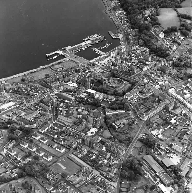 Oblique aerial view of Rothesay, taken from the SW, centred on the town.  The harbour is visible in the top right side of the photograph.   The castle and the Winter Gardens are visible in the centre of the photograph.