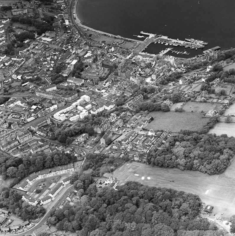 Oblique aerial view of Rothesay, taken from the S, centred on the town.  A harbour is visible in top right-hand side of the photograph.  A castle and the Winter Gardens are visible in the top centre of the photograph.