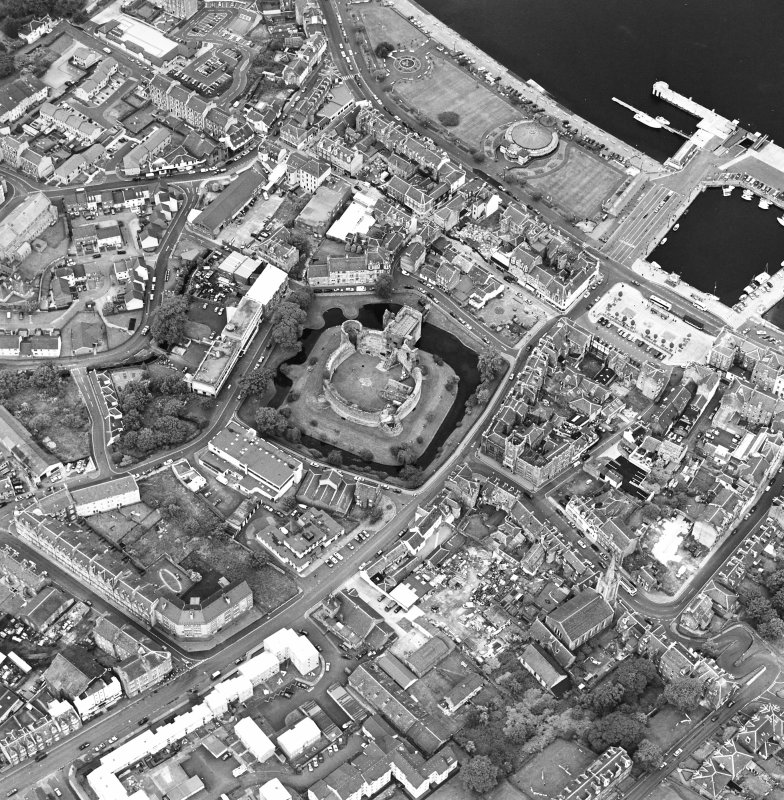 Oblique aerial view of Rothesay, taken from the SE, centred on a castle.  The Winter Gardens is visible in the top centre of the photograph.  The photograph gives a general view of the town.