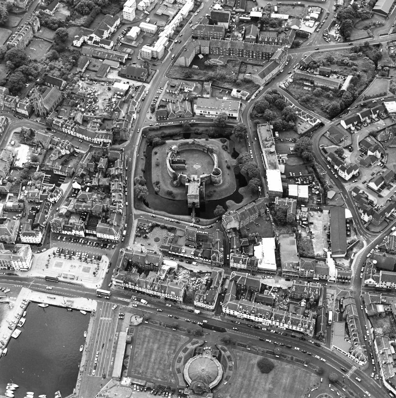 Oblique aerial view of Rothesay, taken from the N, centred on a castle. The Winter Gardens is visible in the bottom centre of the photograph. The photograph gives a general view of the town.