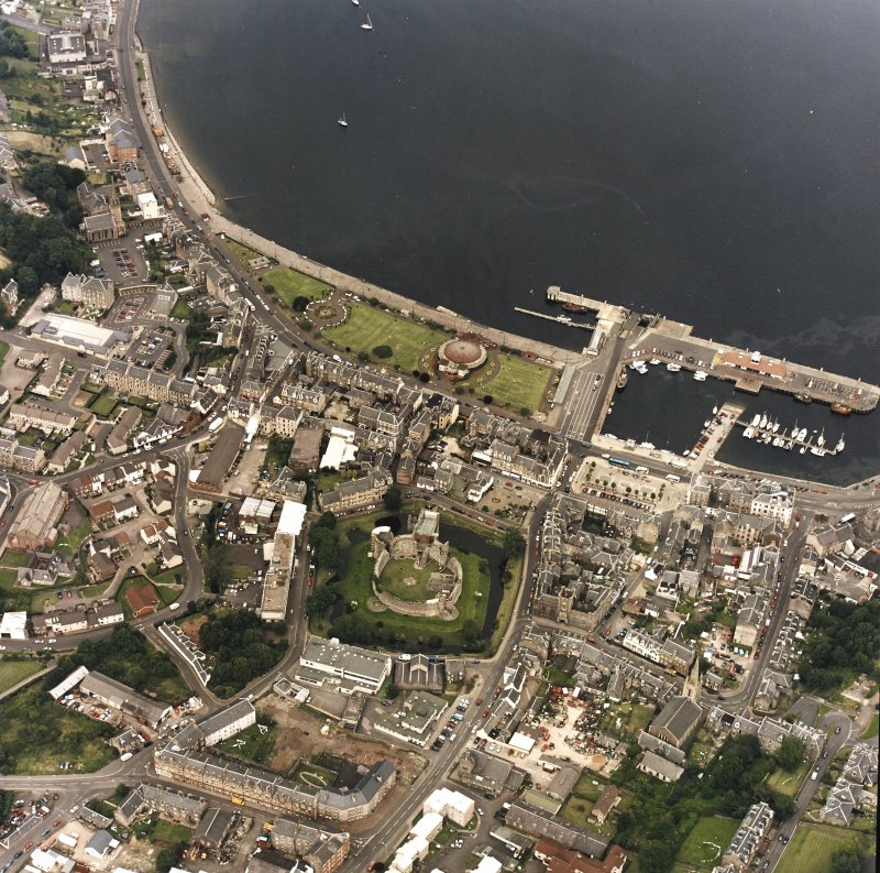 General oblique aerial view of Rothesay centred on the remains of the castle, the harbour and winter gardens, taken from the SSE.