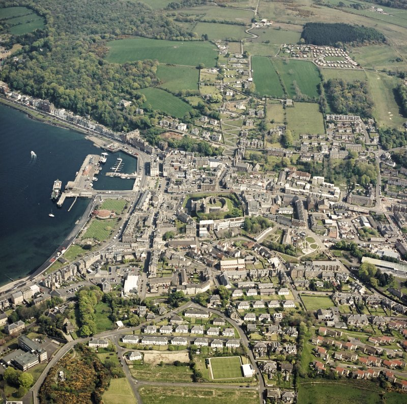 General oblique aerial view of Rothesay centred on the remains of the castle and chapel, with the winter gardens and pier adjacent taken from the W.