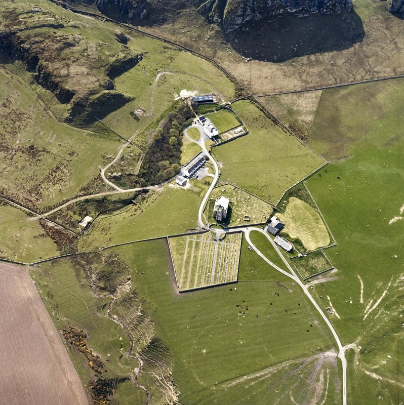Oblique aerial view of Kilchoman centred on the church, burial-grounds and manse, taken from the NW.