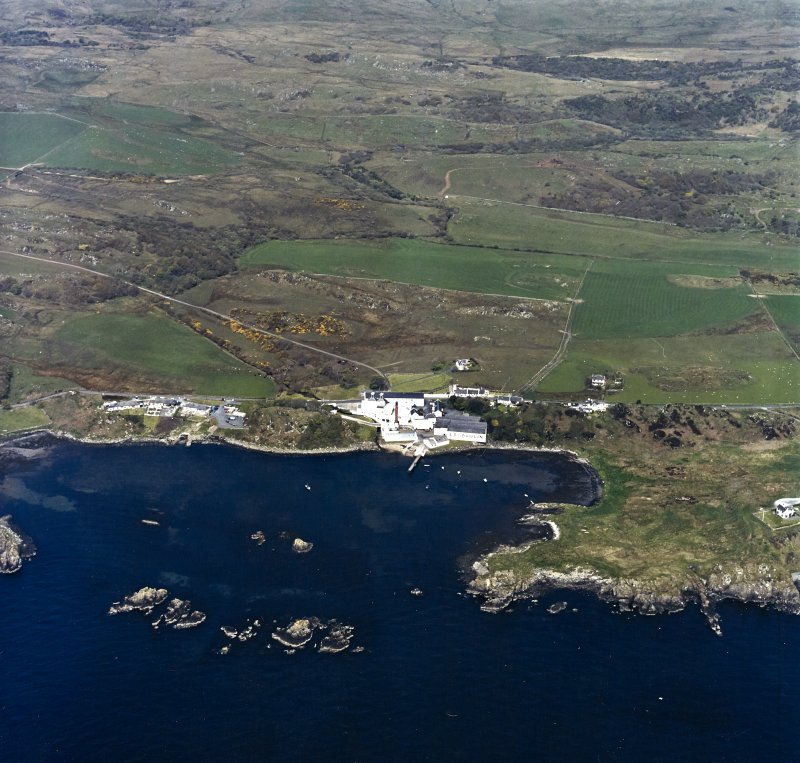 Oblique aerial view centred on the whisky distillery, pier and cottages with the remains of the castle adjacent, taken from the SSE.
