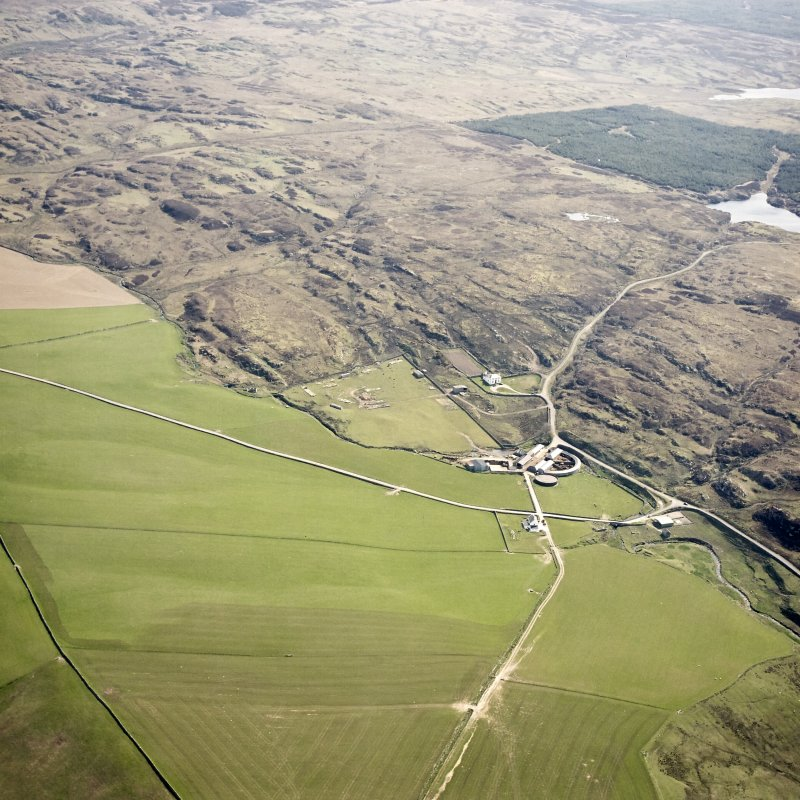 Oblique aerial view centred on the farmhouse, farmsteading, engine house and hut, taken from the W.