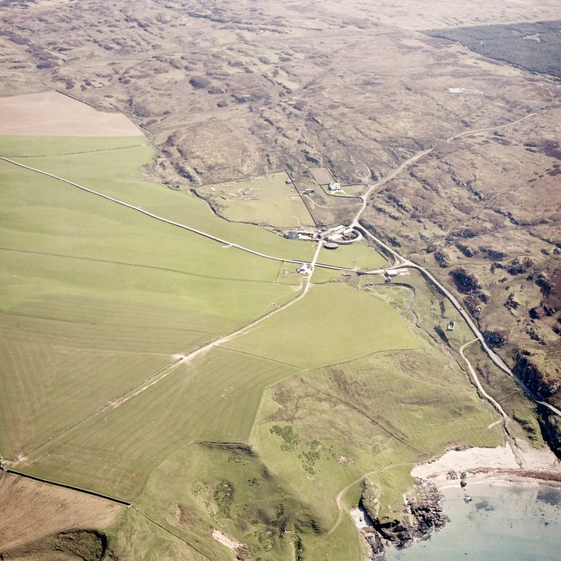 Oblique aerial view centred on the farmhouse, farmsteading, engine house and hut with the remains of the chapel and rig adjacent, taken from the W.