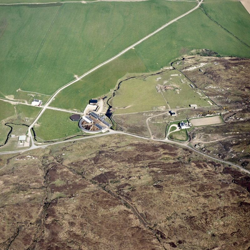 Oblique aerial view centred on the farmhouse, farmsteading, engine house and hut, taken from the SE.