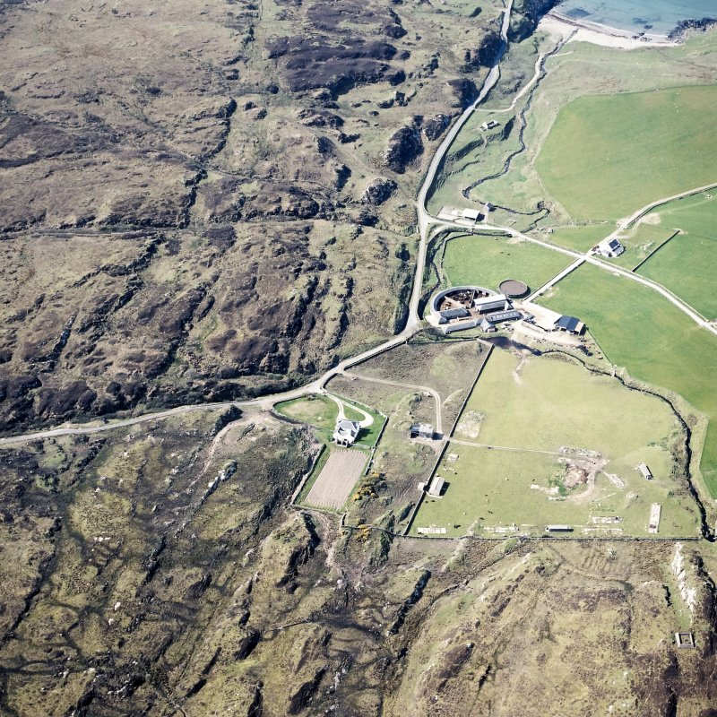 Oblique aerial view centred on the farmhouse, farmsteading, engine house and hut, taken from the NE.