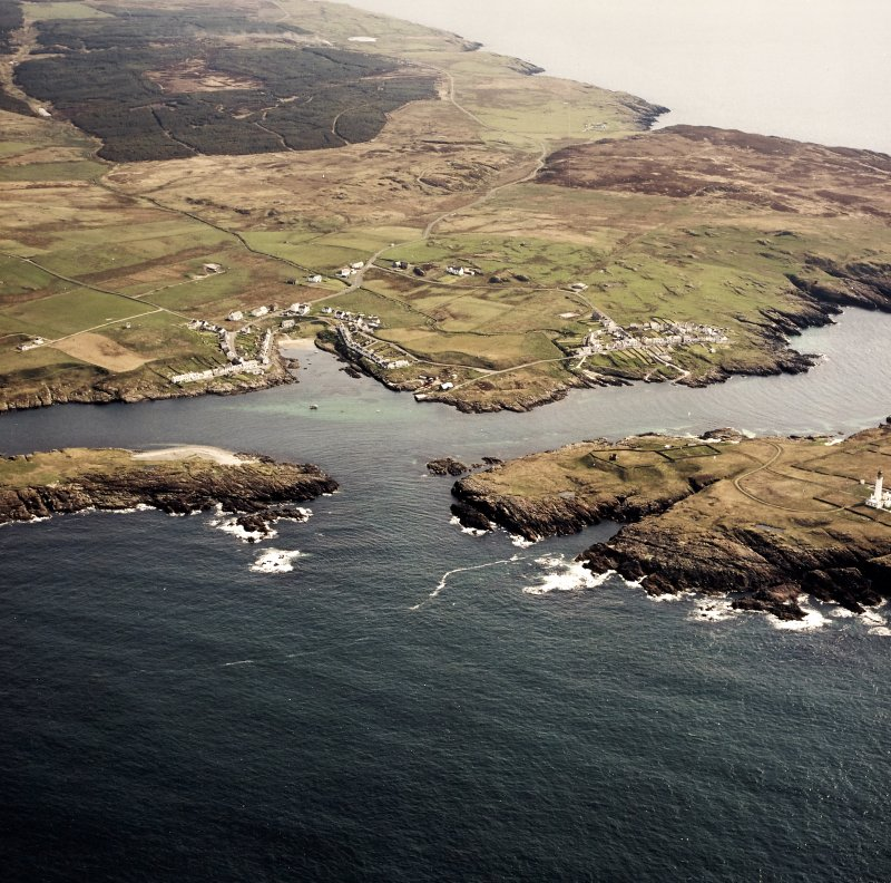 General oblique aerial view centred on the villages, lighthouse, cottage and remains of the chapel and burial ground, taken from the WSW.