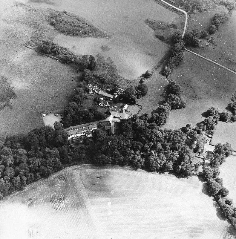 Oblique aerial view centred on the church, churchyard and hotel, taken from the WNW.