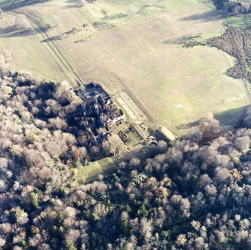 Oblique aerial view centred on the remains of the country house and gardens, taken from the NW.