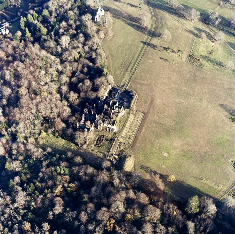 Oblique aerial view centred on the remains of the country house with the church adjacent, taken from the WSW.