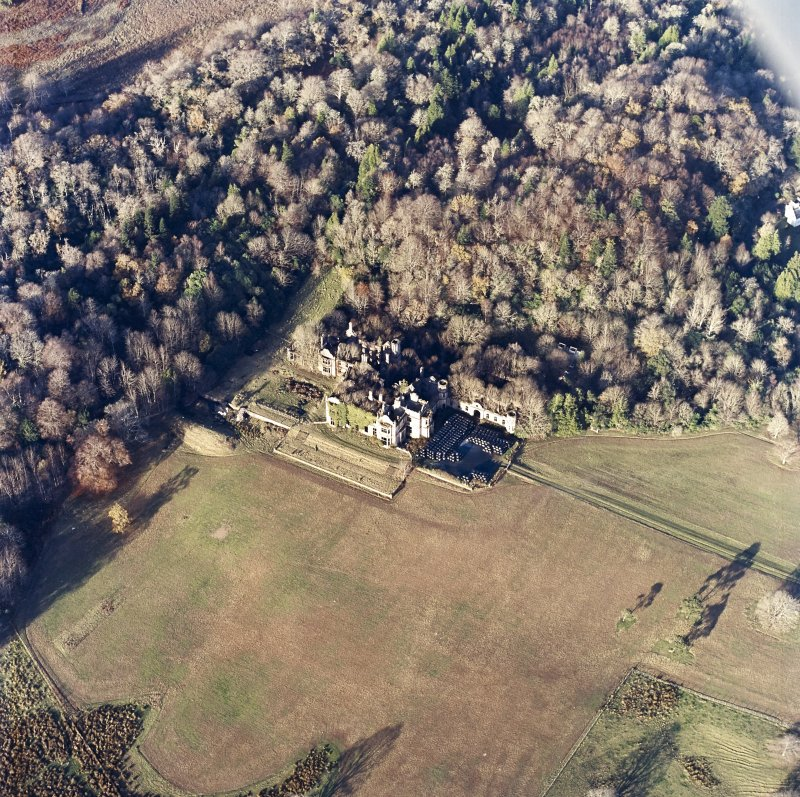 Oblique aerial view centred on the remains of the country house and gardens, taken from the SSE.