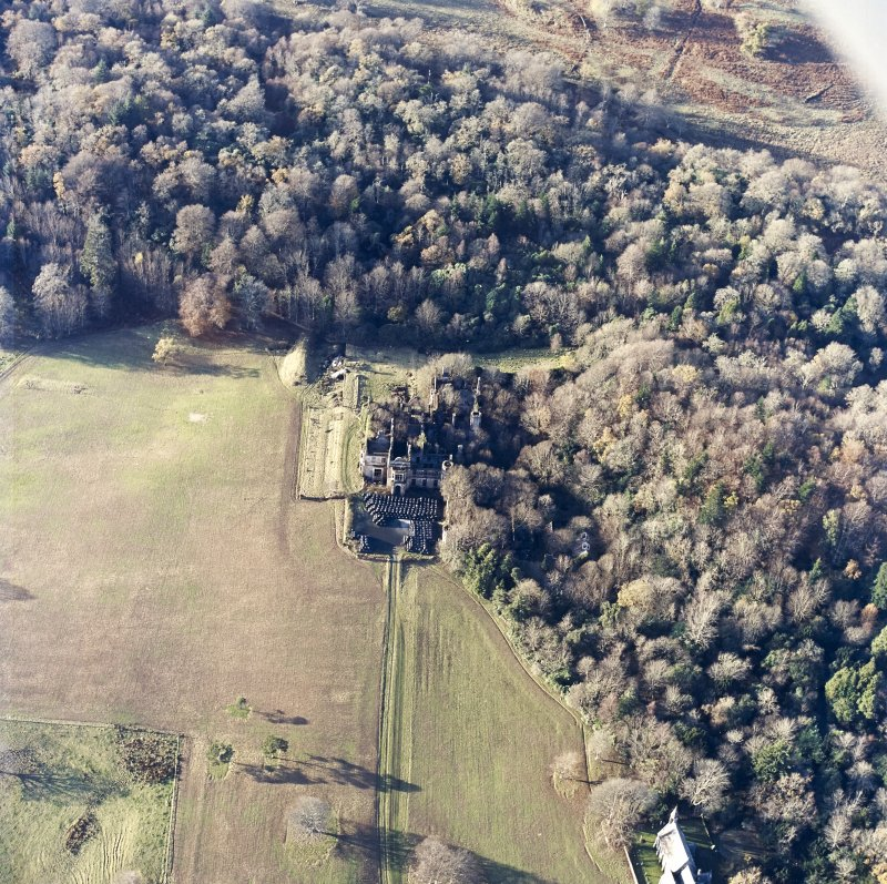 Oblique aerial view centred on the remains of the country house with the church adjacent, taken from the ESE.
